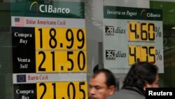 People walk past a board displaying the exchange rate for Mexican peso against the U.S. dollar and the euro in a Bank in Mexico City, Mexico, Nov. 15, 2016.