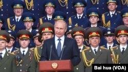 俄羅斯總統普京去年夏季在一次對外軍事活動上發表講話。背景是亞歷山大紅旗歌舞團。