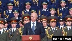 俄罗斯总统普京去年夏季在一次对外军事活动上发表讲话。背景是亚历山大红旗歌舞团。