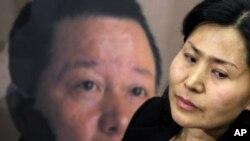 Bà Cảnh Hòa, vợ của luật sư nhân quyền Cao Trí Thịnh (hình phía sau) tại một cuộc họp báo ở thủ đô Washington (ảnh tư liệu, ngày 18/1/2011)