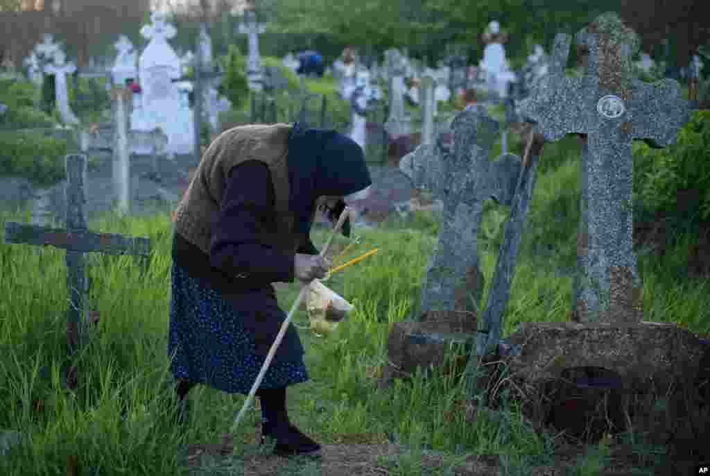 An elderly woman walks to a relative's grave at dawn in Copaciu, Romania.