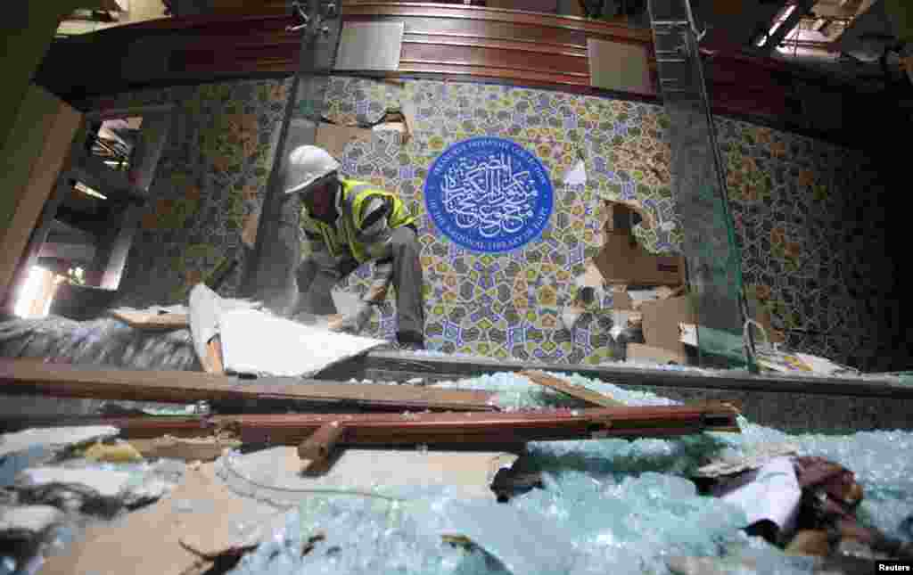 An antiquities restoration worker moves broken glass at the Egyptian National Library and Archives, which was damaged by a car bomb attack targeting the nearby Cairo Security Directorate, Cairo, Jan. 26, 2014.