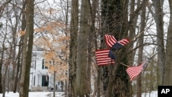 """Small American flags have been placed in the trees in front of the Warmbier family home, Friday, Jan. 22, 2016, in Wyoming, Ohio. North Korea on Friday announced the arrest of Otto Warmbier, a university student from Ohio, for what it called a """"hostile act"""" orchestrated by the American government to undermine the authoritarian nation."""