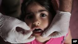 Bé Rose Mohammed, 4 tuổi, uống vaccine ngừa bại liệt ở Baghdad, Iraq.