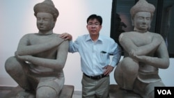 Kong Vireak, the director of the National Museum of Cambodia, with two of the returned statues known as the Kneeling Attendants, Phnom Penh, June 30, 2014. (Robert Carmichael/VOA)
