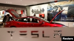 FILE - A man looks around Tesla Motors' Model S P85 at its showroom in Beijing, China.