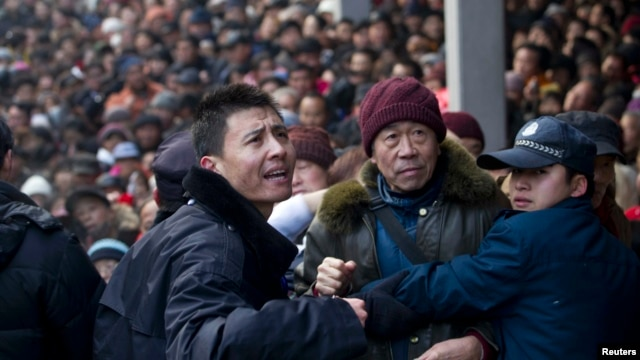 FILE  - Security personnel try to control the crowd as locals visit the Lingyin Temple during the Laba Festival in Hangzhou, Zhejiang province January 19, 2013.