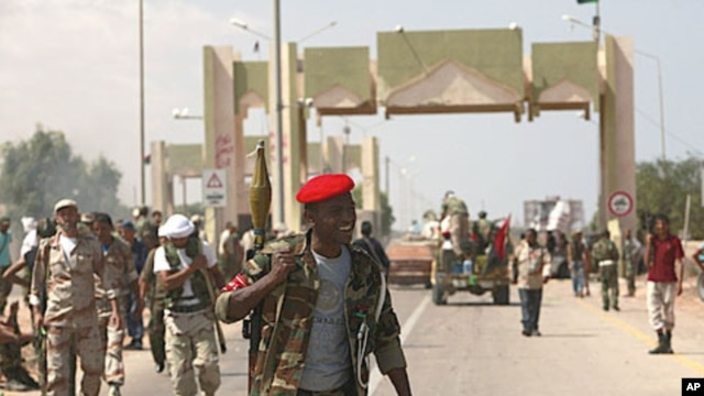 Anti-Gaddafi fighters stand guard after they took over El-Khamseen gate, the eastern gate of Sirte, Libya, September 24, 2011.