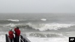 People watch the waves in a rainstorm at the Atlantic Ocean at Carolina Beach, North Carolina, Oct. 2, 2015.