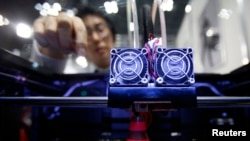 FILE - A staff member of Nihonbinary demonstrates their 3D printer MakerBot Replicator 2X as it prints an Acrylonitrile butadiene styrene pylon during the International Robot Exhibition 2013 in Tokyo, Nov. 8, 2013.