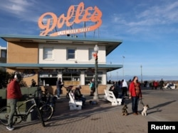 FILE - People try to keep a social distance due to the coronavirus disease (COVID-19) pandemic as they gather on the boardwalk in Rehoboth Beach, Delaware, U.S. January 2, 2021. (REUTERS/Jonathan Ernst)