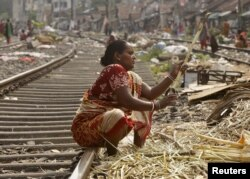 A woman peels sugarcanes on a railway track to sell it to sugarcane juice vendors at a slum area in Kolkata, India May 10, 2015.
