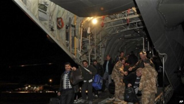 In this photo released by Britain's Ministry of Defense, civilians disembark from one of two Royal Air Force C130 Hercules that evacuated more than 150 civilians from desert locations south of Benghazi, at Malta's international airport, February 27, 2011