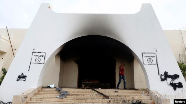 A man walks at the headquarters of Islamist militant group Ansar al-Sharia after it was set on fire by protesters after clashes between members of the group and a Libyan army special forces unit in the Ras Obeida area in Benghazi, Nov. 25, 2013.