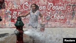 A girl cools off from the heat in water from an open fire hydrant in the Washington Heights section of upper Manhattan in New York City, New York, U.S., July 19, 2019. (REUTERS/Mike Segar)