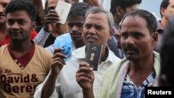 تجمع کارگران خارجی در برابر یک اداره کار در ریاض. کارگران پس از انقضای مهلت تمدید ویزا گذرنامه شان را در دست دارند