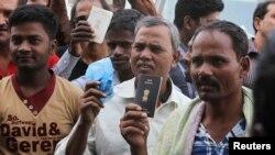 2013年11月4日,在沙特首都利雅得的一个劳工办公室,外籍劳工手持护照要求延期签证