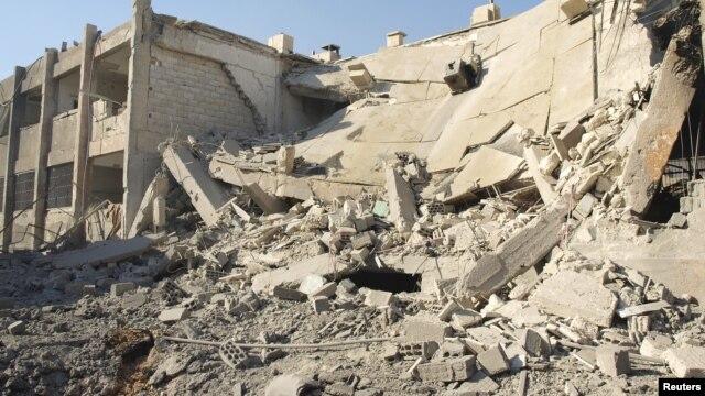 Các tòa nhà bị hư hại, theo lời các nhà hoạt động, vì các cuộc oanh kích của máy bay của lực lượng không quân trung thành với Tổng thống al-Assad
