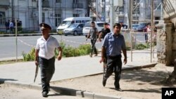 Police officers secure an area in the capital of Tajikistan, Dushanbe, where several Interior Ministry special forces officers and a traffic policeman were reportedly shot dead, Sept. 4, 2015.