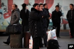 A migrant worker smokes as others wait for their trains at the Beijing railway station in Beijing, Monday, Jan. 21, 2019. China's economic growth hit a three-decade low in 2018.