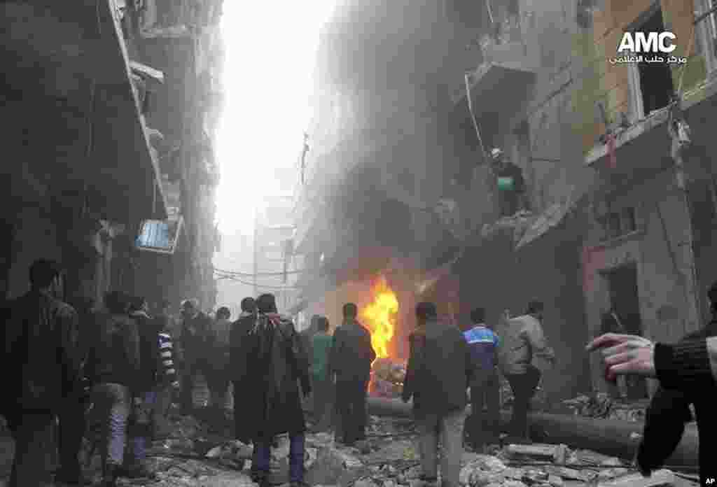 This citizen journalism image provided by Aleppo Media Center shows Syrians gathering around damaged buildings while others try to extinguish fires following a government airstrike in Aleppo, Dec. 15, 2013.