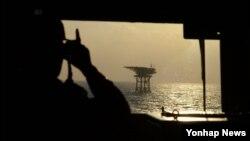 지난 2일 한국 이지스함인 율곡이이함에서 한 승조원이 이어도에 세워져 있는 종합해양과학기지를 망원경으로 지켜보고 있다.