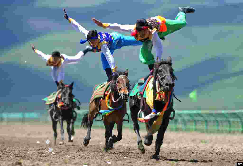 Riders wearing ethnic group costume compete in a traditional horseback riding event in Hongyuan county of Aba town, or Ngawa town, southwest China's Sichuan province, June 17, 2014.