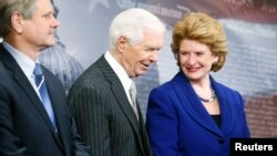U.S. Senate Agriculture Committee Chairman Debbie Stabenow (D-MI) smiles with ranking member Senator Thad Cochrane (R-MI) (C) at a news conference after the final passage of the Farm Bill at the U.S. Capitol in Washington, Feb. 4, 2014.