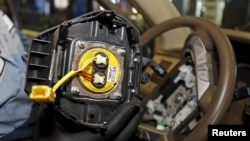 FILE - A recalled Takata airbag inflator, removed from a Honda Pilot, is shown at the AutoNation Honda dealership service department in Miami, Florida, June 25, 2015.