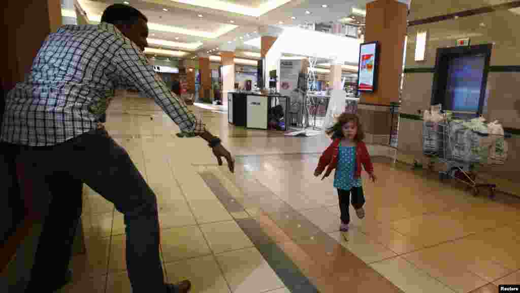 A child runs to safety as armed police hunt gunmen who went on a shooting spree at Westgate shopping center in Nairobi, Kenya, Sep. 21, 2013. The gunmen stormed a shopping mall, killing at least 20 people in what the government said could be a terrorist attack.