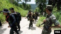 Seorang tentara Kamboja (kanan) mengamati para tentara Thailand yang melewati perbatasan yang disengketakan (foto: dok.)