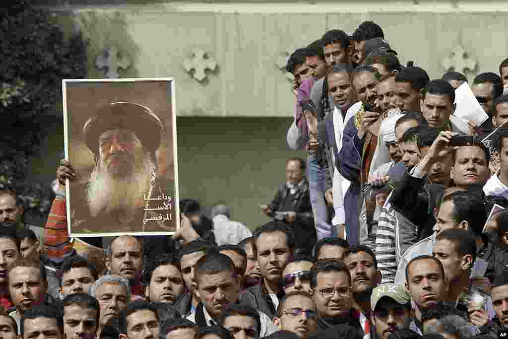 Egyptian Christians watch the funeral of Pope Shenouda, seen in the poster at left, at St. Mark Coptic Orthodox Church in Cairo, March 20, 2012. (AP)