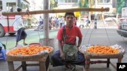 一个男孩12月5日在仰光的街头出售水果