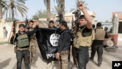 FILE - Iraqi security forces celebrate as they hold a flag of the Islamic State group they captured in Ramadi, Iraq.