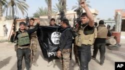Lực lượng an ninh Iraq ăn mừng khi giữ một lá cờ của nhóm Nhà nước Hồi giáo mà họ đã bắt ở Ramadi, 70 dặm (115 km) về phía tây Baghdad, Iraq.