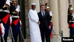 FILE - French President Emmanuel Macron welcomes Chadian President Idriss Déby as he arrives to attend an international conference on Libya at the Elysee Palace in Paris, May 29, 2018.
