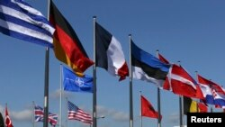 FILE - Flags fly at the Alliance headquarters in Brussels during a NATO ambassadors meeting on the situation in Ukraine and the Crimea region.