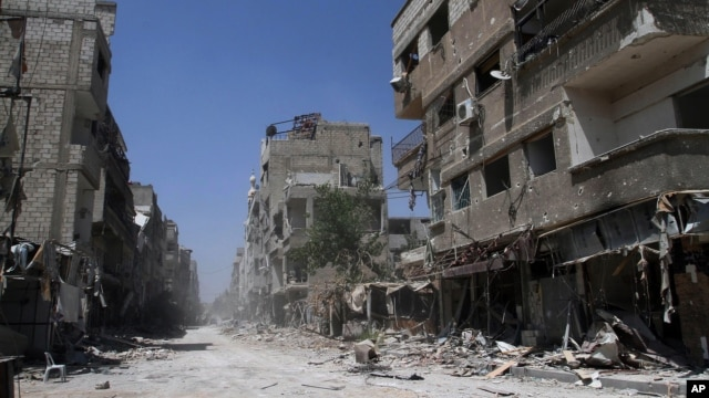 In this photo taken during a Syrian government-led media tour, buildings damaged during battles between Syrian troops and rebels stand along an empty street in Mleiha, about 10 kilometers (6 miles) southeast of downtown Damascus, Syria, Aug. 15, 2014.