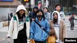 芝加哥中國城的一位女性1月30日戴口罩步行。