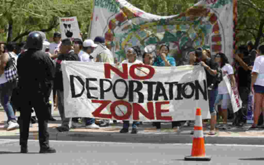 Protesters, against SB 1070, hold signs up in front of the Phoenix courthouse in Phoenix, Arizona, July 29, 2010. Arizona brought in a weakened anti-immigration law on Thursday after a U.S. court blocked its most intrusive provisions and analysts said the