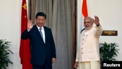India's Prime Minister Narendra Modi (R) and China's President Xi Jinping wave to the media during a photo opportunity ahead of their meeting at Hyderabad House in New Delhi, Sept. 18, 2014.