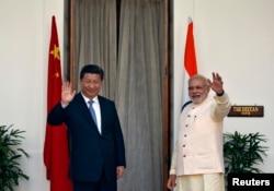 印度总理莫迪(右) 与中国国家主席习近平(左)在星期四会谈前向媒体挥手致意