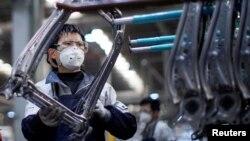 戴着口罩的工人在上海延锋安道拓工厂汽车座椅的生产线上工作。(2020年2月24日)