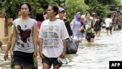 Phụ nữ Indonesia lội qua một con đường ngập lụt ở Tangerang, ngày 27/10/2010