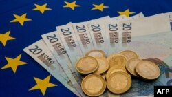 A picture taken on June 29, 2015 in Lille shows Drachma bills, Greece's former currency, next to euro bills and coins.