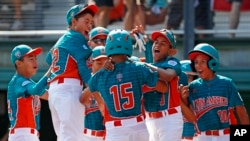 Maracaibo, Venezuela's Jonney Rosario (15) celebrates with teammates after hitting a two-run home run during the first inning of an International pool play baseball game against White Rock, British Columbia. (AP Photo/Gene J. Puskar)