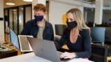 Kelly Soderlund, right, works with another employee at the TripActions office in San Francisco, Friday, Aug. 27, 2021. (AP Photo/Eric Risberg)