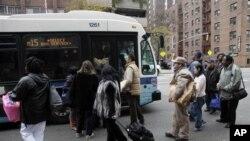Hành khách ở New York đón xe buýt. Vì hệ thống xe điện ngầm chưa hoạt động nên xe buýt rất đông khách