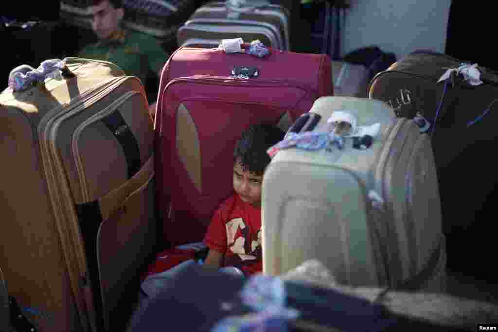 A Palestinian boy rests among suitcases as he waits to cross into Egypt at Rafah crossing between Egypt and southern Gaza Strip.