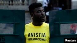 FILE - An Amnesty International activist shouts slogans in Rio de Janeiro, Brazil, April 1, 2014.